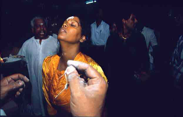 A devotee in a state of trance as she prepares herself to be pierced on her forehead