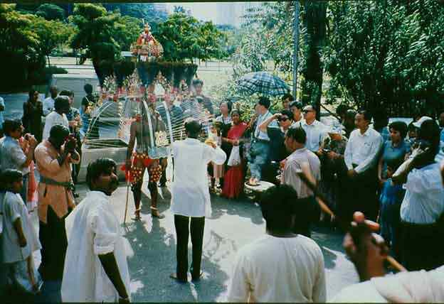 Family and friends cheer on as a devotee approaches the Thandayudhapani temple, Tank Road