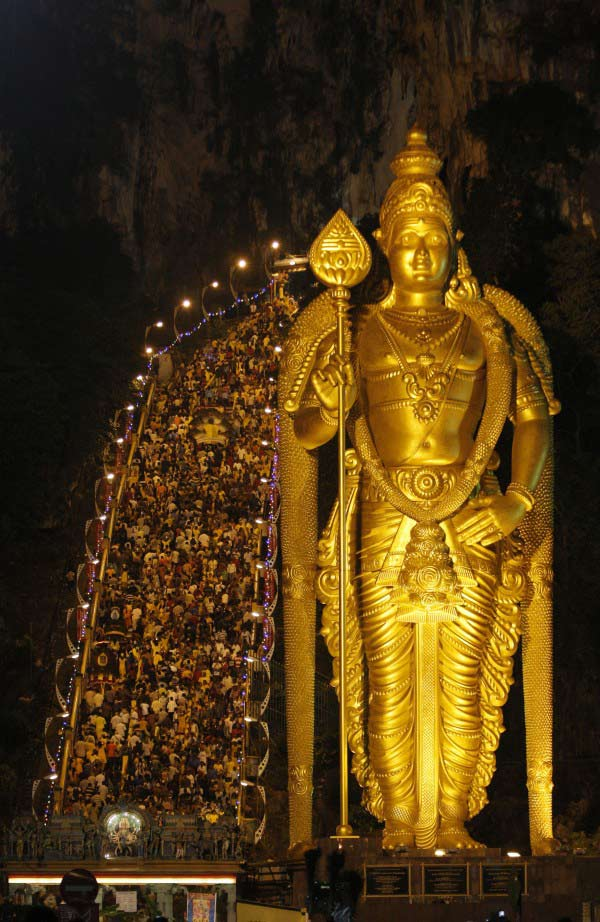 Hindu devotees climb 272 steps to the Batu Caves temple next to a giant statue of Lord Murugan during the Thaipusam festival